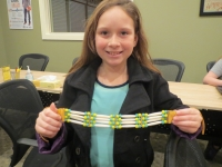 Cow Creek student holds up a finished necklace