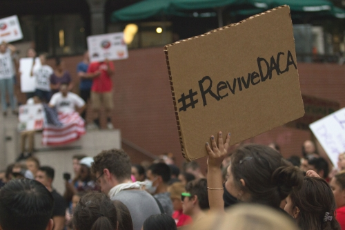 A cardboard protest sign with #RevivieDACA written in permanent marker is the only thing in focus amid a crowd of people