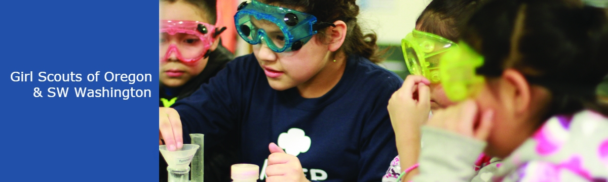 Three girl scouts wearing lab goggles and working on an experiment