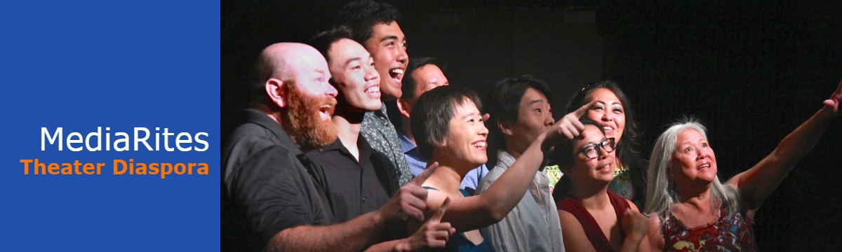 A group of Asian actors stand on the stage looking and pointing to the side